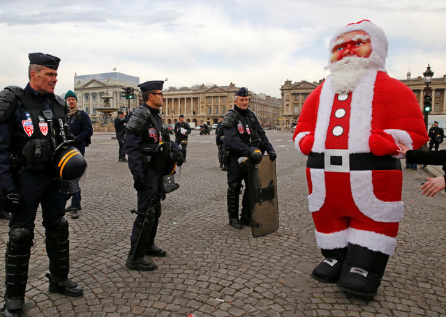 French CRS riot police stand next to a giant inflatable Santa Claus during a demonstration by Paris fairground stallholders to block the Place de la Concorde, in protest over the state's demand that the famous Ferris wheel lording over the square be taken down, in Paris, France, November 24, 2016. (Photo by Jacky Naegelen/Reuters)