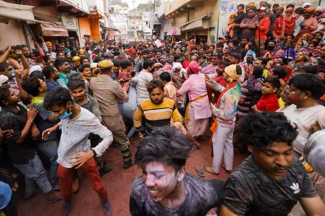 Police officers and locals try to control the crowd during Lathmar Holi celebrations in the town of Barsana, northern state of Uttar Pradesh, India, March 23, 2021. (Photo by Adnan Abidi/Reuters)