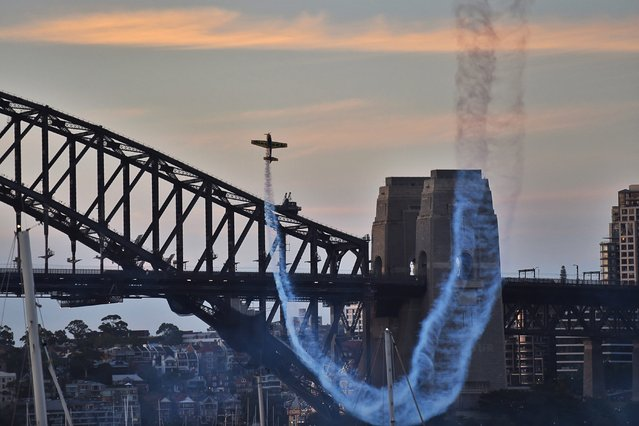 An acrobatic racing plane trails smoke prior to the New Year's Eve fireworks in Sydney, Australia, 31 December 2015. (Photo by Mick Tsikas/EPA)