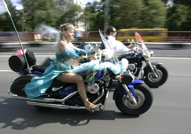 Yevgeni Okayevich (R) and his bride Galina Grann ride their motorbikes during their wedding in central Kiev July 5, 2008. (Photo by Konstantin Chernichkin/Reuters)