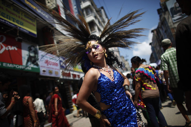 A participant poses in a Gay Pride rally in Katmandu, Nepal, Thursday, August 22, 2013. About 1,000 people, including gays, lesbians, transvestites and their supporters hold the rally that has now become an annual festival for sexual minorities to celebrate and to demand rights for their community. Organizers said the rally was an opportunity for the sexual minorities to come out in the open and also to educate the public. (Photo by Niranjan Shrestha/AP Photo)