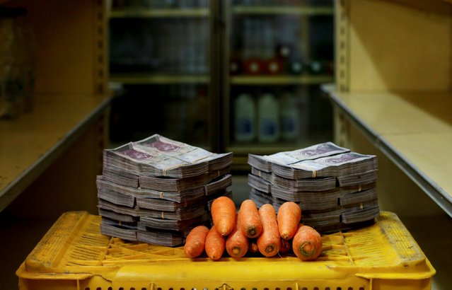 A kilogram of carrots is pictured next to 3,000,000 bolivars, its price and the equivalent of 0.46 USD, at a mini-market in Caracas, Venezuela August 16, 2018. It was the going price at an informal market in the low-income neighborhood of Catia. (Photo by Carlos Garcia Rawlins/Reuters)