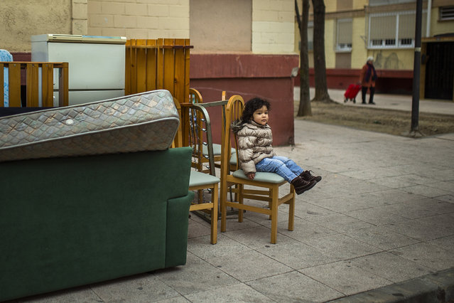 Diana Sofia Meliton, 2 years old, sits outside with her family's belongings after they got evicted by the police in Madrid, Spain, Wednesday, February 11, 2015. Pablo Henrique Meliton, 39 years old, his wife Damaris Varela Rivera, 36 yeas old , and their daughter Diana Sofia Meliton, 2 years old, lived in an occupied Bankia bank apartment for a year, as they couldn't afford to pay rent. (Photo by Andres Kudacki/AP Photo)