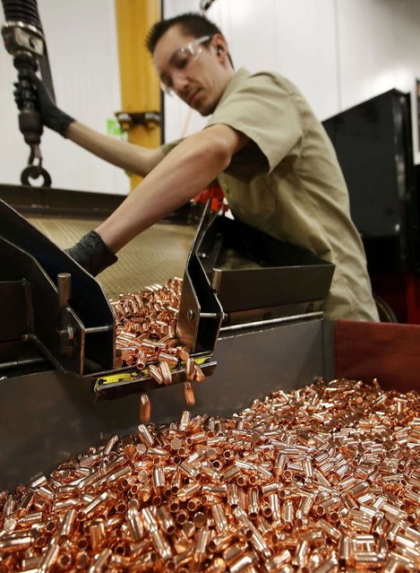 A worker transfers newly washed bullet casings into a large bin at Barnes Bullets in Mona, Utah, January 6, 2015. (Photo by George Frey/Reuters)