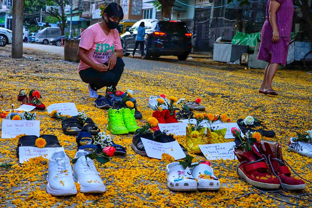 """This photo taken and received courtesy of an anonymous source on April 8, 2021 show a woman looking at shoes displayed with flowers in Yangon's Myaynigone township, as part of the """"Marching Shoes Strike"""" called on social media to protest against the demonstration against the military coup in Myanmar. (Photo by Handout via AFP Photo)"""