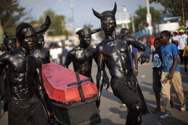 Revelers dressed as devils with their bodies smothered in clay mud and oil, parade through the streets hauling a coffin, at the start of Carnival celebrations in Port-au-Prince, Haiti, Sunday, February 15, 2015. (Photo by Dieu Nalio Chery/AP Photo)