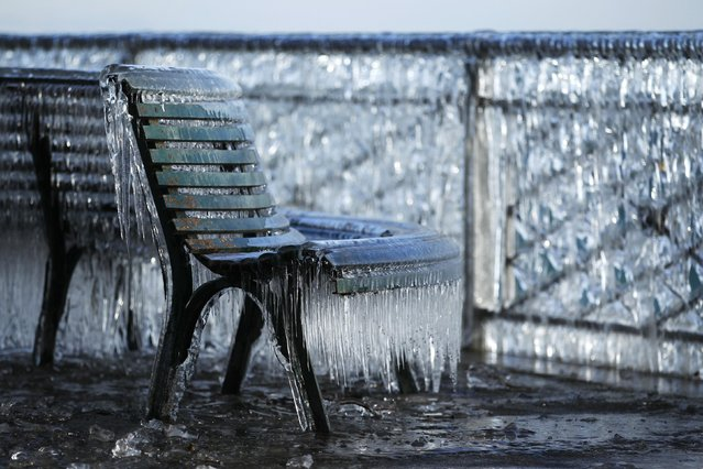 A frozen public bench is seen next to a lake side due to the heavy wind conditions in Geneva February 8, 2015. (Photo by Pierre Albouy/Reuters)