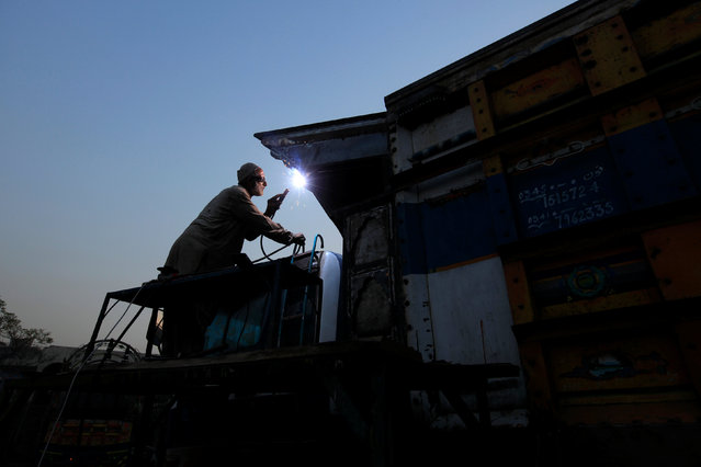 A man welds a truck at a vehicle workshop in Rawalpind, Pakistan, November 10, 2016. (Photo by Faisal Mahmood/Reuters)