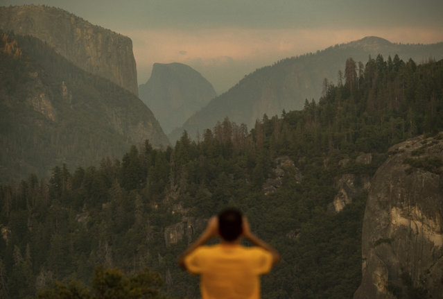Francisco Avendano, visiting from Madrid, Spain, photographs Half Dome as smoke from the Ferguson Fire hangs over Yosemite National Park, Calif., on Tuesday, July 24, 2018. Parts of the park, including Yosemite Valley, will close Wednesday as firefighters work to contain the blaze. (Photo by Noah Berger/AP Photo)