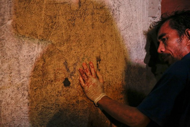 A funeral parlour worker, his hands bloodied from carrying bodies, rests against the wall of a house in Manila, Philippines early November 1, 2016. According to police and witnesses, unknown masked gunmen killed five people inside the house that is a known drug den. (Photo by Damir Sagolj/Reuters)