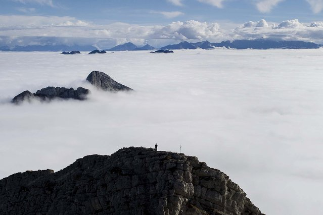 A man watches a sea of clouds as he stands on a side summit of Mount Saentis in Urnaesch, near Appenzell, Switzerland, on Oktober 8, 2013. (Photo by Gian Ehrenzeller/Keystone)