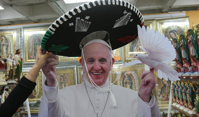 A woman puts a Mariachi Hat on a figure of Pope Francis at a store of the Basilica of Guadalupe Church in Mexico City, Mexico, 19 January 2016. Pope Francis will visit Mexico from 12 to 17 February. (Photo by Mario Guzman/EPA)