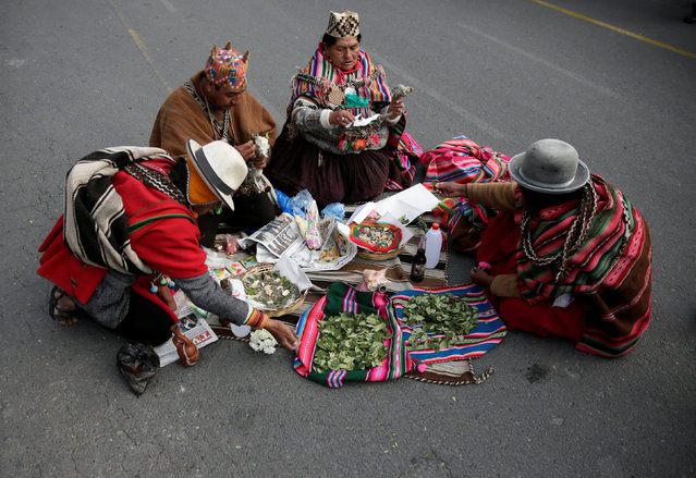 """Aymara witch doctors prepare an offering to blessing the totora reeds """"Viracocha III"""", a boat made only from the reed, as it is being prepared to cross the Pacific from Chile to Australia on an expected six-month journey, in La Paz, Bolivia December 15, 2016. (Photo by David Mercado/Reuters)"""
