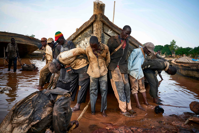Malian workers haul out a boat they use to carry sand collected from the river bed during a routine maintenance on October 7, 2018, in the port of Bamako. (Photo by Michele Cattani/AFP Photo)