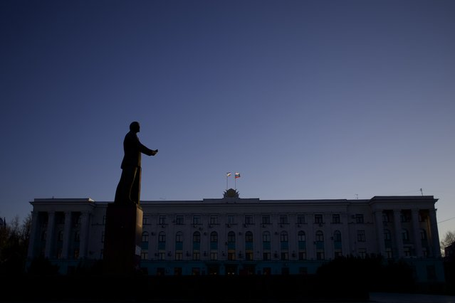 In this Saturday, March 15, 2014 file photo Russian and Crimean flags fly over a local government building as Soviet State founder Vladimir Lenin's statue dominates over landscape in downtown Simferopol, Crimea. (Photo by Ivan Sekretarev/AP Photo)