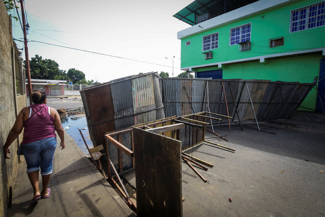 A woman walks on the street next to a makeshift barricade after a demonstration in Ciudad Bolivar, Venezuela December 19, 2016. (Photo by William Urdaneta/Reuters)