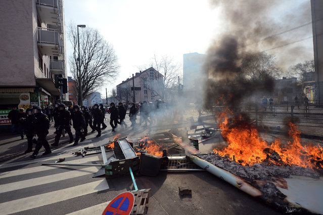 Police walk past a burning barricade during a demonstration organized by the Blockupy movement to protest against the policies of the European Central Bank (ECB) after the ECB officially inaugurated its new headquarters earlier in the day on March 18, 2015 in Frankfurt, Germany. At least 10,000 protesters were expected to take part at riot police equipped with water cannons established a wide security perimeter around the ECB site. (Photo by Thomas Lohnes/Getty Images)