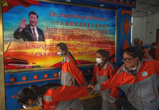 Tibetan students leave class passed a poster showing President Xi Jinping during a government organized visit for journalists to Nagqu High School, an off-site schooling program for students from high altitude areas, on June 1, 2021 in Lhasa, Tibet Autonomous Region, China. (Photo by Kevin Frayer/Getty Images)