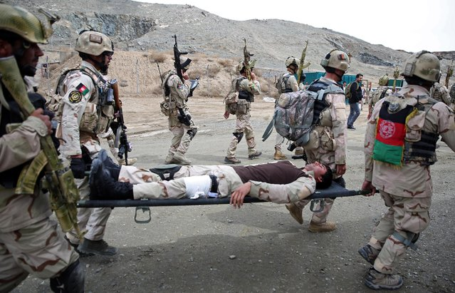 Afghanistan's interior ministry special forces carry their wounded colleague during a military exercise in Kabul, Afghanistan, Thursday, April 2, 2015. (Photo by Massoud Hossaini/AP Photo)