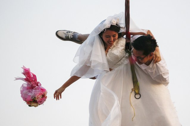 Bride Duangreuthai Amnuayweroj and groom Kasemsak Jiranantiporn throw a bouquet during a wedding ceremony ahead of Valentine's Day at a resort in Ratchaburi province February 13, 2016. (Photo by Athit Perawongmetha/Reuters)