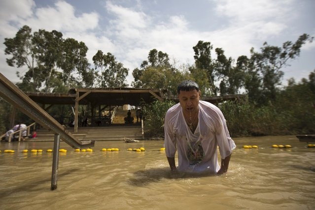 A Christian pilgrim dips in the water during his visit to the baptismal site known as Qasr el-Yahud on the banks of the Jordan River near the West Bank city of Jericho April 9, 2015. (Photo by Amir Cohen/Reuters)