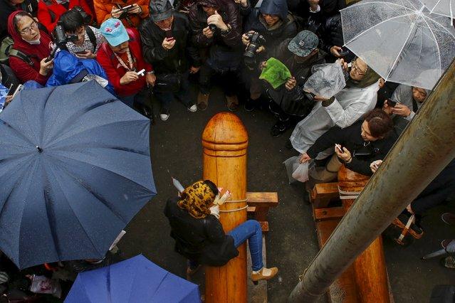 People take pictures as a woman mounts a wooden phallus symbol during the Kanamara Matsuri, or Iron Phallus Festival at the Kanamara shrine in Kawasaki outside of Tokyo April 5, 2015. (Photo by Thomas Peter/Reuters)