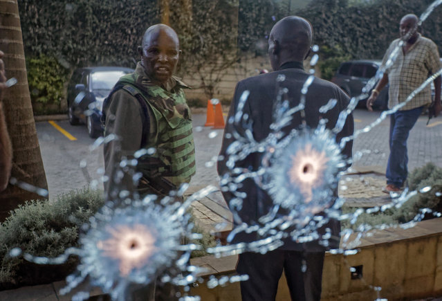 A member of the security forces is seen reflected in a window as he looks at bullet-holes, at a hotel complex in Nairobi, Kenya Tuesday, January 15, 2019. Terrorists attacked an upscale hotel complex in Kenya's capital Tuesday, sending people fleeing in panic as explosions and heavy gunfire reverberated through the neighborhood. (Photo by Ben Curtis/AP Photo)