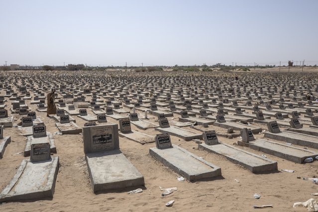 A man walks in a mass graveyard where hundreds of Yemeni fighters are buried in Marib, Yemen, Monday, June 21, 2021. (Photo by Nariman El-Mofty/AP Photo)
