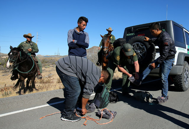U.S. Border Patrol agents from Boulevard Station inspect three men near Jacumba, California, U.S., November 14, 2016. Prisoners participating in the Wild Horse Inmate Program train mustangs that will eventually be adopted by the U.S. Border Patrol, providing the agency with inexpensive but agile horses, and inmates with skills and insights they hope to one day carry with them from prison. At least 80 percent of the U.S. Border Patrol's current stable of 400 horses come from inmate training programs in Arizona, Colorado, Kansas and Nevada. The horses are critical for patrolling the rugged and remote stretches of the Mexican border to detect illegal crossings by migrants and drug trafficking. (Photo by Mike Blake/Reuters)