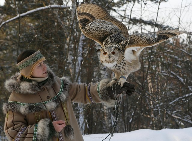 Zoo employee Daria Zhirnova dressed in an Evenki traditional costume, holds Pykh, an 8-month-old eagle owl, during a training session which is a part of Royev Ruchey zoo's programme of taming wild animals for research, and for enlightenment and interaction with visitors, in the Siberian taiga forest in the suburb of Krasnoyarsk, Russia January 10, 2017. (Photo by Ilya Naymushin/Reuters)