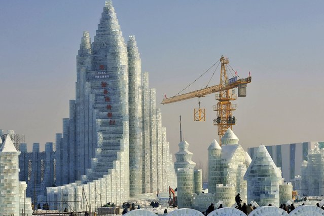 Workers and a crane are seen next to a newly-built ice sculpture of a castle ahead of the 30th Harbin Ice and Snow Festival, in Harbin December 27, 2013. (Photo by Sheng Li /Reuters)