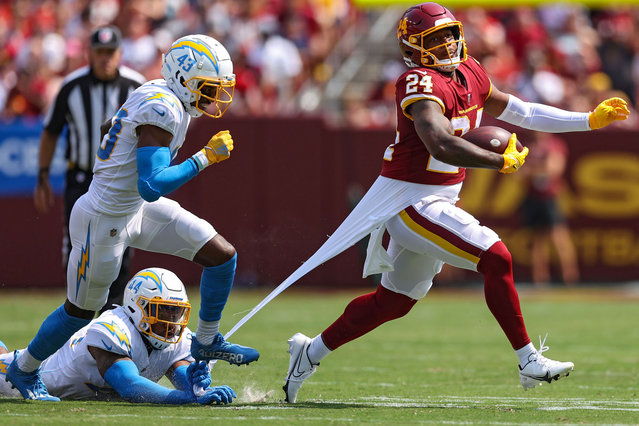 Antonio Gibson #24 of the Washington Football Team rushes past Michael Davis #43 and Kyzir White #44 of the Los Angeles Chargers during the first quarter at FedExField on September 12, 2021 in Landover, Maryland. (Photo by Patrick Smith/Getty Images)