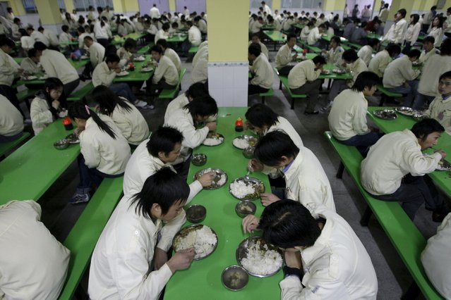 Workers eat dinner at an electronics factory in Dongguan, southern China's Guangdong province in this January 25, 2008 file picture. Rising labor costs, higher real estate prices, less favorable government policies and smaller order volumes are forcing Chinese plants to downsize just to survive. (Photo by Jason Lee/Reuters)