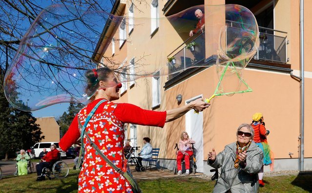 Circus clown Tanja Selmer performs for seniors at their retirement home, as the spread of the coronavirus disease (COVID-19) continues in Jueterbog, south of Berlin, Germany, April 7, 2020. (Photo by Fabrizio Bensch/Reuters)