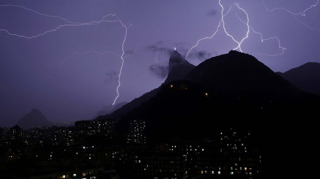 Liightning strikes near Christ the Redeemer statue on January 16, 2014. A violent lightning and rain storm swept across the city, flooding streets, knocking out power and chipping the right thumb of the famed statue. (Photo by Renata Brito/Associated Press)