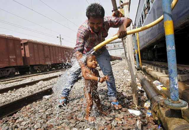 A passenger bathes an child using a pipe that supplies water to trains at a railway station on a hot summer day in the northern Indian city of Allahabad April 23, 2015. Temperatures in Allahabad on Thursday reached to 42 degree Celsius (107.6 degree Fahrenheit), according to India's metrological department website. (Photo by Jitendra Prakash/Reuters)