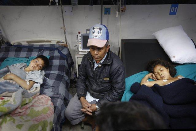A Nepalese man sits near earthquake injured children at a hospital, in Kathmandu, Nepal, Sunday, April 26, 2015. (Photo by Manish Swarup/AP Photo)