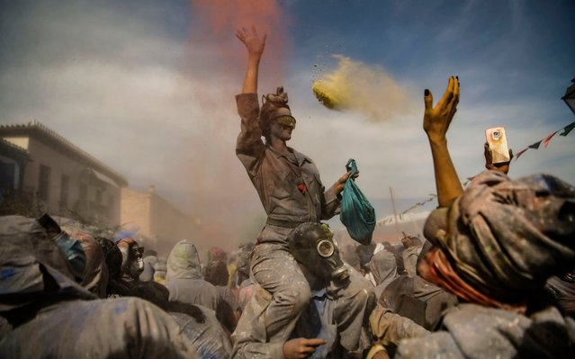 """A Reveller throws coloured flour as she participates in a """"flour war"""" during the """"Ash Monday"""" celebrations, a traditional festivity marking the end of the carnival season and the start of the 40-day Lent period until the Orthodox Easter, in the port town of Galaxidi, Greece, on March 11, 2019. (Photo by Aris Messinis/AFP Photo)"""