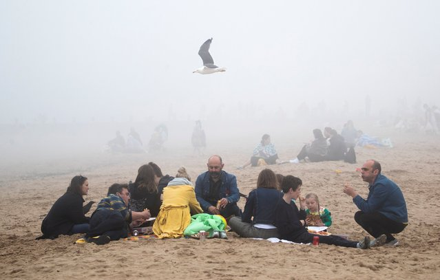 People on Edinburgh's Portobello Beach on May 30, 2021surrounded by mist, with the bank holiday weekend expected to bring blue skies and widespread sunshine most of the east coast of Scotland has experienced haar and sea mist. (Photo by Jane Barlow/PA Images via Getty Images)
