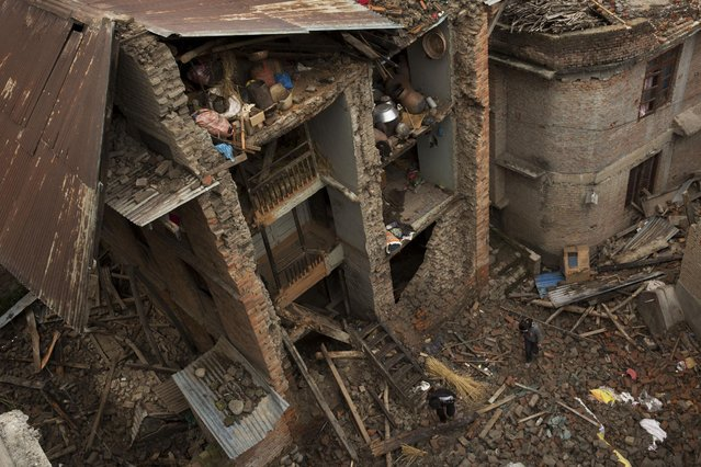People walk past a house with one side of its walls completely destroyed by Saturday's earthquake in Sakhu, on the outskirts of Kathmandu, Nepal, Wednesday, April 29, 2015. (Photo by Bernat Amangue/AP Photo)