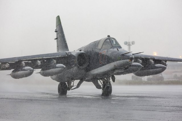 A Russian Sukhoi Su-25 fighter jet is seen on a runway in the rain shortly before taking off, part of the withdrawal of Russian troops from Syria, at Hmeymim airbase, Syria, March 16, 2016. (Photo by Vadim Grishankin/Reuters/Russian Ministry of Defence)
