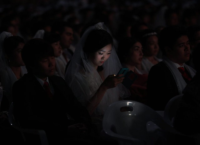 A bride looks at her smartphone in a mass wedding ceremony at the CheongShim Peace World Center in Gapyeong, South Korea, Wednesday, February 12, 2014. (Photo by Lee Jin-man/AP Photo)