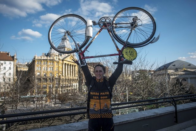 Bicycle courier Aliz Szaloky holds her bike above her head on the roof of a commercial building in Budapest, Hungary, 26 February 2016. (Photo by Bea Kallos/EPA)