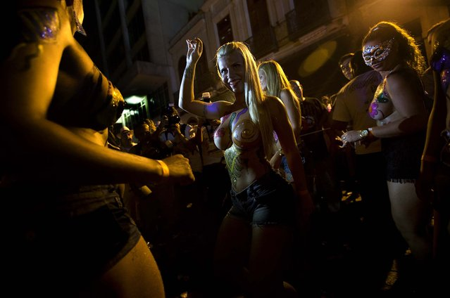 "Women wearing body paint dance at the ""Rua do Mercado"" band Carnival parade in Rio de Janeiro, February 27. The women said they were topless to defend the right of women to be topless on Rio's beaches, as they joined one of many parades before the official start of Carnival on February 28. (Photo by Silvia Izquierdo/Associated Press)"