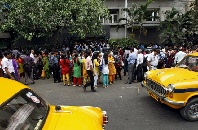 People stand outside a office building after vacating it following an earthquake in Kolkata, India, May 12, 2015. (Photo by Rupak De Chowdhuri/Reuters)