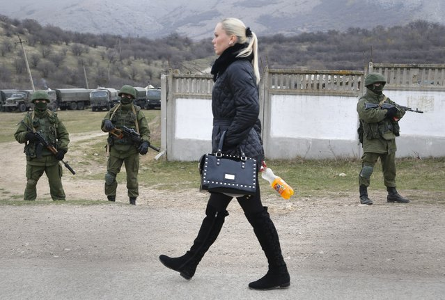A woman passes pro Russian troops at Ukraine's infantry base in Perevalne, Ukraine, Tuesday, March 4, 2014. Russian President Vladimir Putin said Moscow reserves the right to use all means to protect Russians in Ukraine as U.S. Secretary of State John Kerry was on his way to Kiev. Tensions remained high in the strategic Ukrainian peninsula of Crimea with troops loyal to Moscow firing warning shots to ward off protesting Ukrainian soldiers. (Photo by Sergei Grits/AP Photo)