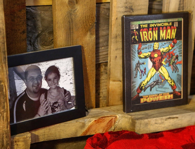 In this photo taken April 8, 2015, A picture of Clay Hielscher and daughter Kyrianna sits on a shelf in their Overbrook, Kan., home next to a canvas print of an Iron Man comic book cover. (Photo by Chris Neal/AP Photo/The Topeka Capital-Journal)