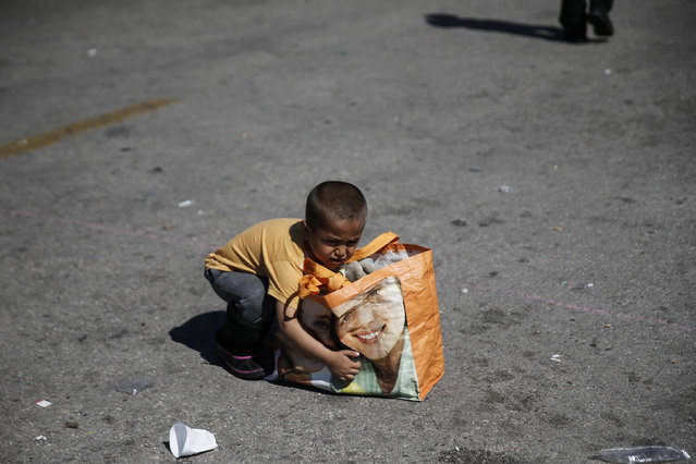 A child prepares to lift a bag before boarding a bus heading to other parts of the country where refugees and migrants will be accommodated, at the port of Piraeus, near Athens, Greece March 31, 2016. (Photo by Alkis Konstantinidis/Reuters)