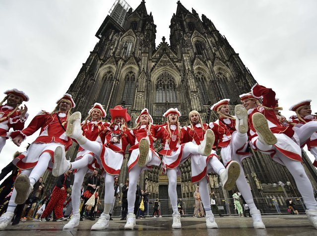Male dancers perform in front of the world famous Cologne cathedral when tens of thousands revelers dressed in carnival costumes celebrate the start of the street-carnival in  Cologne, Germany, Thursday, February 23, 2017. (Photo by Martin Meissner/AP Photo)