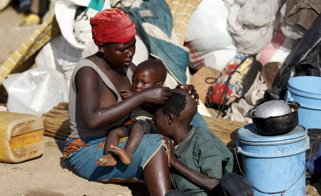 A Burundian refugee shaves her son as they gather on the shores of Lake Tanganyika in Kagunga village in Kigoma region in western Tanzania with their belongings, as they wait for MV Liemba to transport them to Kigoma township, May 17, 2015. (Photo by Thomas Mukoya/Reuters)
